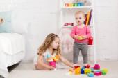 Fotografie rozkošný sestry hrát s konstruktor v místnosti dětí