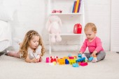 Fotografie adorable sisters playing with constructor on carpet in children room