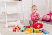 Rozkošné dítě hraje s lékárničku v místnosti dětí