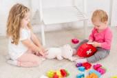 erhöhte Ansicht der entzückenden Schwestern spielen mit Spielzeug im Kinderzimmer