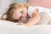 šklebící se rozkošný šťastné dítě ležící na posteli v pokoji dětí a při pohledu na fotoaparát