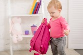 adorable kid in pink shirt carrying pink bag in children room