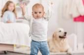 Fotografie lustige liebenswert Kind stehend mit erhobenen Händen und Blick in die Kamera im Kinderzimmer
