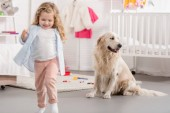 Fotografie cheerful adorable kid and golden retriever in children room