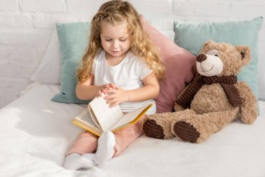 Adorable child playing with teddy bear and reading book on bed in children room stock vector
