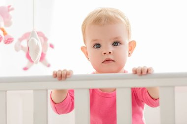 adorable toddler in pink shirt standing in crib and looking at camera