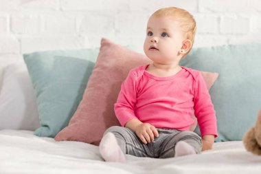 adorable kid sitting on bed with pillows and looking up in children room