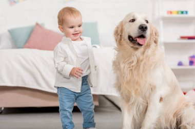 smiling adorable kid looking at golden retriever dog in children room