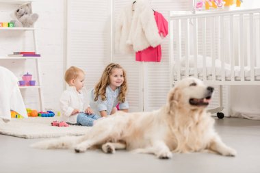 selective focus of cheerful adorable sisters playing on floor, golden retriever lying near in children room