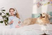 Fényképek imádnivaló kid hallgat zenét a gyermekek szobában ágyon tabletta, golden retriever