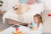 vista di alto angolo di adorabile bambino che gioca con i cubi di educativi, carino cane sdraiato sul letto in camera bambini