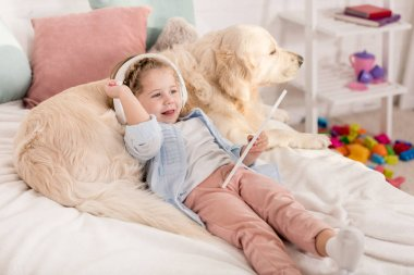 adorable kid using tablet and leaning on golden retriever on bed in children room