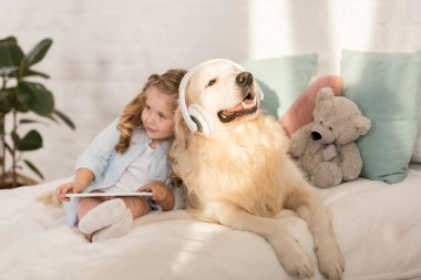 adorable child holding tablet, cute golden retriever with headphones lying on bed in children room