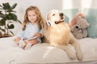 adorable kid holding tablet, funny golden retriever with headphones lying on bed in children room