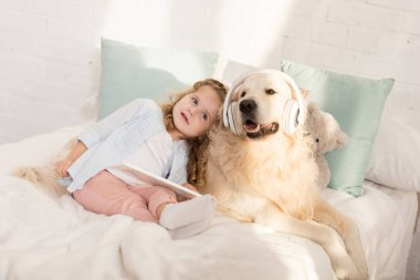 adorable child holding tablet and leaning on fluffy golden retriever with headphones lying on bed in children room