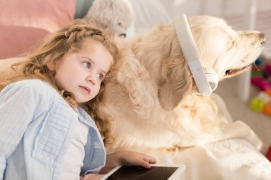 adorable preschooler holding tablet and leaning on cute dog with headphones lying on bed in children room