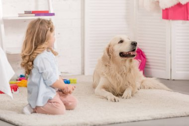 adorable kid and golden retriever sitting on carpet in children room