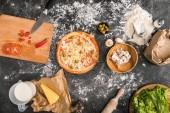 pohled shora tepelně neupravené pizzu, kuchyňské náčiní a přísady na šedém pozadí s moukou