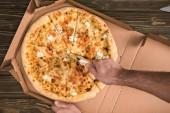 částečný pohled člověka řezání sýr pizza s nožem na dřevěný stůl