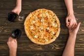 Fotografie abgeschnittene Ansicht eines Paares, das Hände und Rotweingläser hält, während es Pizza auf einem Holztisch isst
