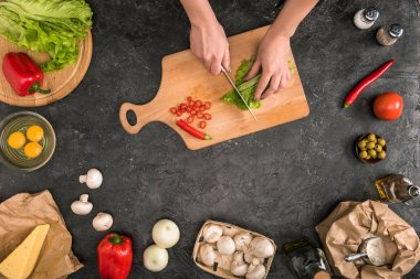 cropped view of woman chopping vegetables on cutting board with pizza ingredients on grey background