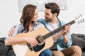 couple sitting on couch and playing acoustic guitar at home