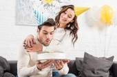 muž foukání svíčky na narozeninový dort s usmívající se žena v pařbu na pozadí