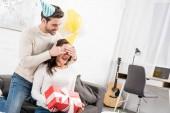 Fotografie Mann in Partyhut Augen zu schließen und die Geburtstagsüberraschung mit Geschenk für erregte Frau zu Hause