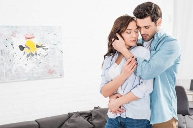 handsome man tenderly embracing woman at home
