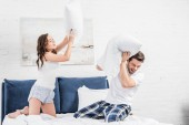 couple in pajamas fighting with pillows in bedroom