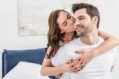 žena něžně objímat a líbat pohledný muž v posteli