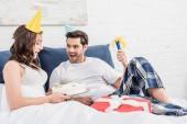 Aufgeregtes Paar in Partyhüten liegt im Bett und feiert Geburtstag zu Hause mit Kuchen und Partyhorn