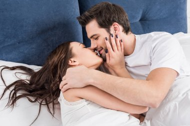 beautiful couple in nightwear kissing in bed at home