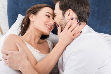 smiling couple embracing and looking at each other in bed