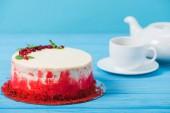 torta decorata con ribes rosso e foglie di menta vicino bianco tazza e teiera isolato sullazzurro