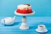 torta díszítik a piros ribiszke és a menta levelek, a fehér kupa és a teáskanna kék elszigetelt