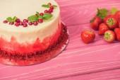 zblízka bílý dort zdobený červený rybíz a mátou poblíž jahody