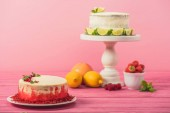 Fotografie cake decorated with currants and mint leaves near fruits and white cake on pink wooden surface isolated on pink