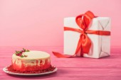 Fotografia torta decorata con ribes e foglie di menta vicino a contenitore di regalo rosa