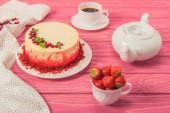 Chiuda in su della torta decorata con ribes e foglie di menta vicino teiera e tazza di fragole