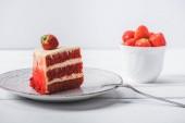 Fotografie kus červené koláče zdobené s jahodou na talíř u šálku ovoce izolované na bílém