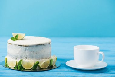 cake decorated with slices of lime near tea cup isolated on blue