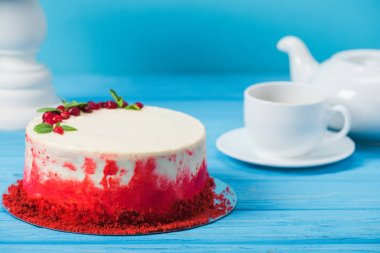 cake decorated with red currants and mint leaves between white cup, tea pot and stand isolated on blue