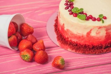 close up of white cake decorated with currants and mint leaves near fruits on pink wooden surface