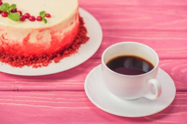 close up of cake decorated with currants and mint leaves near cup of coffee
