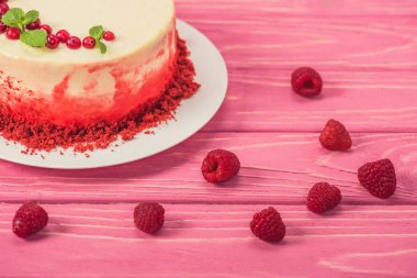 close up of cake decorated with currants and mint leaves near raspberries