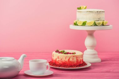 cakes decorated with currants, mint leaves and lime slices near cup and tea pot on wooden surface isolated on pink