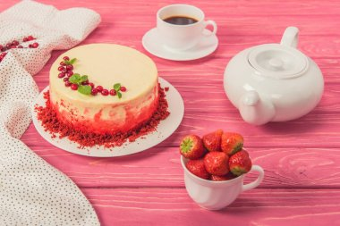 close up of cake decorated with currants and mint leaves near tea pot and cup of strawberries