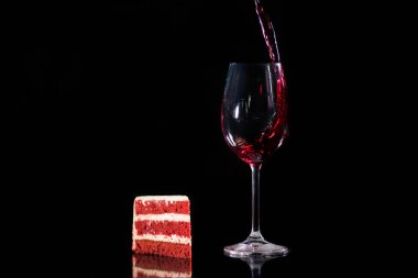 Piece cake near glass of red wine isolated on black stock vector