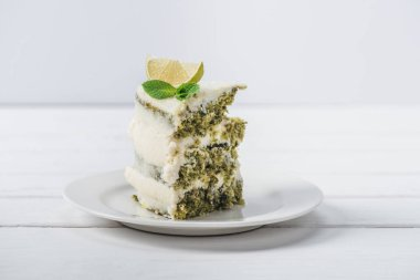 piece of white cake decorated with mint leaves and line slices isolated on white